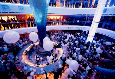 Guests aboard Carnival Horizon enjoy the Electric White Night Party in the cruise liner's main atrium highlighted by the Dreamscapes LED sculpture. Photo by Andy Newman/Carnival Cruise Line