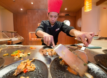 A chef aboard the Carnival Horizon serves entrees to guests during dinner at the Bonsai Teppanyaki that offers a menu of authentic delicacies from the Far East prepared by highly skilled chefs creating dishes on custom-built stations that form the center of the venueÕs two eight-seat tables. Photo by Andy Newman/Carnival Cruise Line