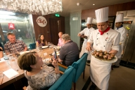 A Carnival Horizon chef serves smoked lamb to guests at the Chef's Table. Located just off the main galley, the Chef's Table offers a multi-course, full-service dinner with cocktails and hors dÕoeuvres for a select group of 14 guests. Photo by Andy Newman/Carnival Cruise Line