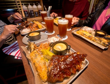 Dinner entrees on the Carnival Horizon at GuyÕs Pig & Anchor Smokehouse|Brewhouse. The venue serves up barbecue favorites created by Food Network star Guy Fieri, as well as four new craft beers brewed on board. Photo by Andy Newman/Carnival Cruise Line