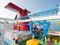 A guest aboard the Carnival Horizon pedals a SkyRide vehicle around much of the 133,500-ton cruise liner. Photo by Andy Newman/Carnival Cruise Line