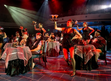 """Carnival Horizon singers/dancesr interact with costumed guests during """"Vintage Pop,"""" a Playlist Productions' revue that evokes the set of a speakeasy in the Great Gatsby and Cotton Club era. The show is led by a toe-tapping, live band in vibrant costumes and includes a burlesque number. Photo by Andy Newman/Carnival Cruise Line"""